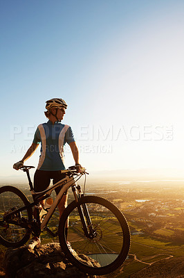 Buy stock photo Full length shot of a woman looking at the view whule cycling in the mountains