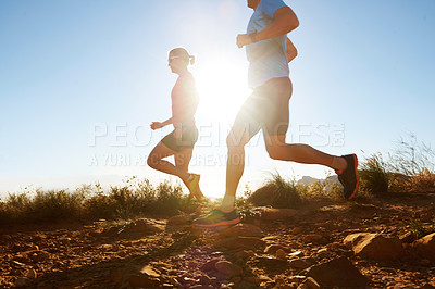 Buy stock photo Cropped shot of a two athletes running on off road terrain