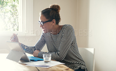 Buy stock photo Cropped shot of an attractive young student working on her digital tablet at home