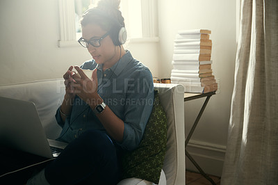 Buy stock photo Cropped shot of an attractive young woman listing to music while sitting on her sofa