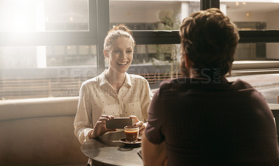 Buy stock photo Shot of a young couple having a chat over coffee