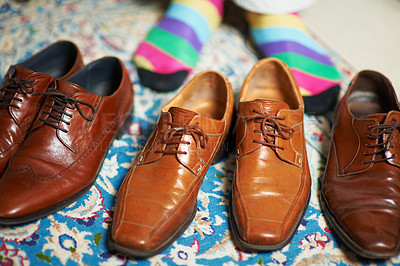 Buy stock photo Cropped shot of a man in colourful socks standing behind 3 pairs of leather loafers
