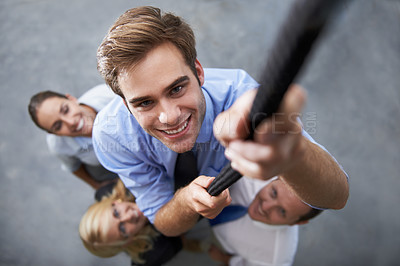Buy stock photo A group of businesspeople cheering on their colleague who is climbing up a rope