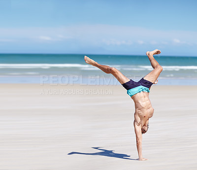 Buy stock photo Young man doing a hand stand on the beach