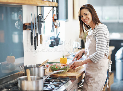 Buy stock photo Portrait of a mature woman preparing a meal in her kitchen