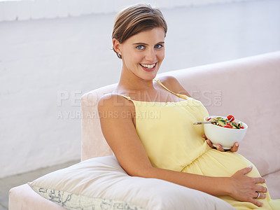 Buy stock photo Shot of a beautiful pregnant woman relaxing on the sofa while eating a fresh salad