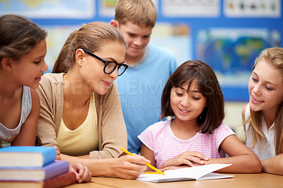 Buy stock photo Shot of a teacher helping her students with their work in the classroom