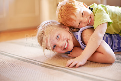 Buy stock photo Shot of an adorable brother and sister playing together on the floor at home