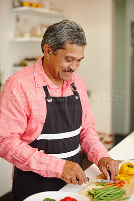 Buy stock photo Shot of a happy senior man cooking a healthy meal at home