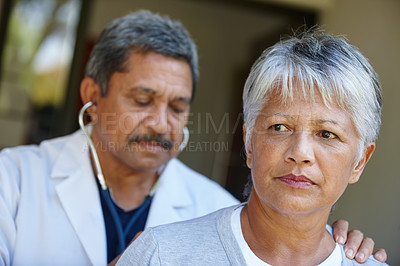 Buy stock photo Cropped shot of a senior woman getting a checkup from her doctor at home