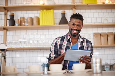 Buy stock photo Cropped shot of a coffee shop owner using a tablet while working in his cafe