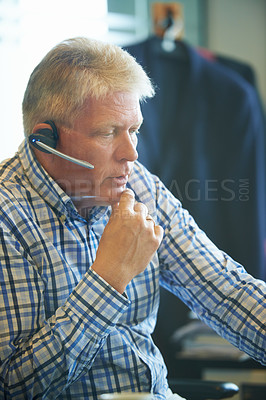 Buy stock photo Shot of a senior businessman wearing a headset looking thoughtful while sitting at his desk