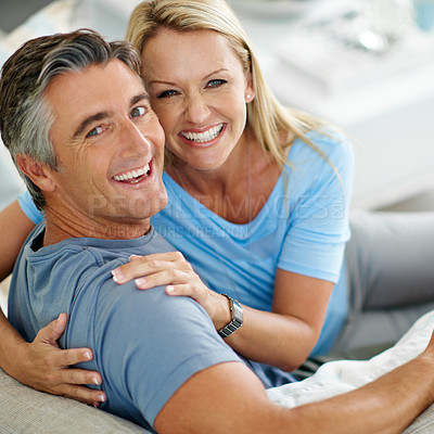 Buy stock photo Shot of a mature couple laughing while relaxing at home