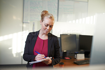 Buy stock photo Cropped shot of an attractive businesswoman making notes in the office