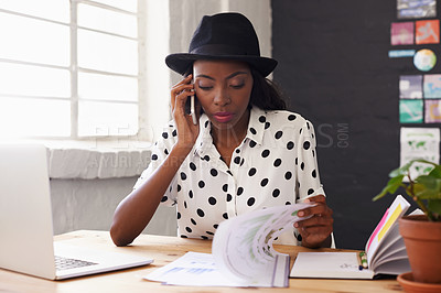 Buy stock photo Shot of a woman talking on her cellphone while going through some paperwork in her office