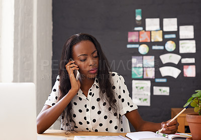 Buy stock photo Shot of a young woman talking on her cellphone while making a note in her diary