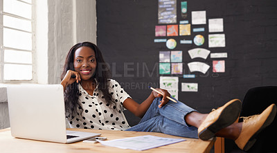 Buy stock photo Shot of a young woman relaxing in her office behind her laptop