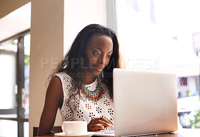 Buy stock photo Shot of an attractive young woman using a laptop in a cafe