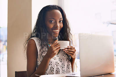 Buy stock photo Shot of an attractive young woman drinking coffee while using a laptop in a cafe