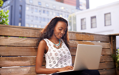 Buy stock photo Shot of a young woman using a laptop outside