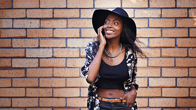 Buy stock photo Shot of an attractive woman talking on her mobile phone against a brick wall