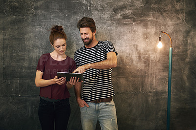 Buy stock photo Cropped shot of two young people using a tablet against a grunge background
