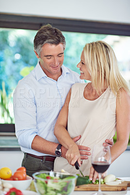 Buy stock photo Cropped shot of an affectionate couple cooking dinner