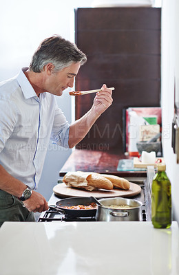 Buy stock photo Shot of a mature man cooking in the kitchen