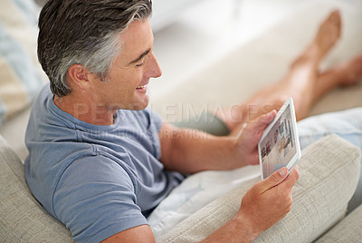 Buy stock photo Shot of a handsome mature man using a digital tablet while relaxing at home