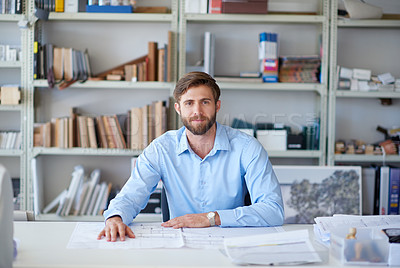 Buy stock photo Portrait of a handsome young architect sitting at his desk with blueprints in front of him