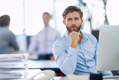 Buy stock photo Portrait of a handsome young businessman sitting at his office desk