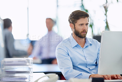 Buy stock photo Shot of a handsome young businessman working at his office computer