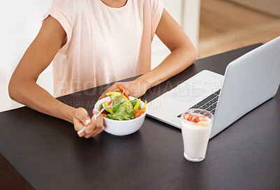 Buy stock photo Cropped shot of a young woman enjoying a salad and working on a laptop at home