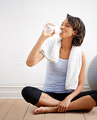 Buy stock photo Shot of a beautiful young woman enjoying a drink of water during a yoga session