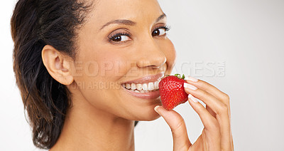 Buy stock photo Portrait of a young woman enjoying some strawberries