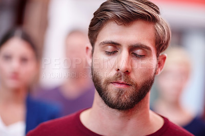 Buy stock photo Shot of an office worker standing with his eyes closed with coworkers in the background
