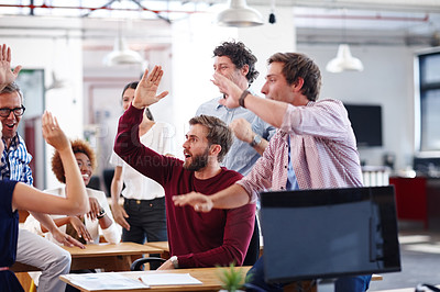 Buy stock photo A group of excited designers celebrating a success during an informal office meeting