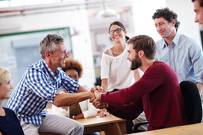 Buy stock photo A mature businessman shaking hands with a colleague during an informal office meeting