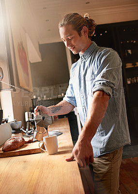 Buy stock photo Shot of a handsome young man having some coffee at home