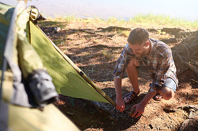 Buy stock photo Shot of a young man setting up a tent while on a camping trip