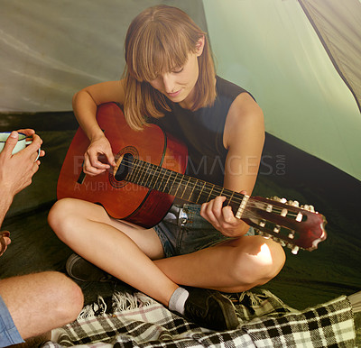 Buy stock photo Shot of a young woman playing guitar to her boyfriend in a tent