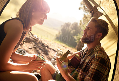 Buy stock photo Shot of a young man playing guitar to his girlfriend in a tent