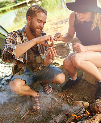 Buy stock photo Shot of a young couple making smores while camping