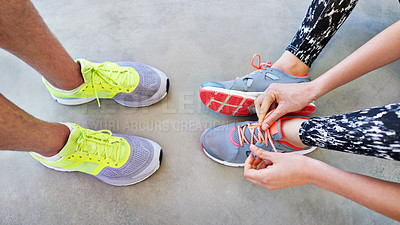 Buy stock photo High angle shot of two people tying their shoelaces before a workout