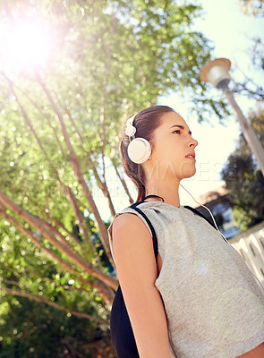 Buy stock photo Shot of a sporty young woman listening to music on her way to the gym