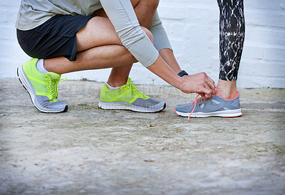 Buy stock photo Shot of a young man tying his girlfriend's shoelaces before a workout