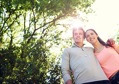 Buy stock photo Shot of a sporty young couple walking together in nature
