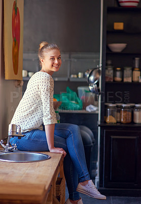 Buy stock photo Shot of a young woman sitting in her kitchen