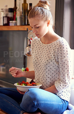 Buy stock photo Shot of a young woman eating a healthy salad in her kitchen