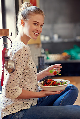 Buy stock photo Portrait of a young woman eating a healthy salad in her kitchen